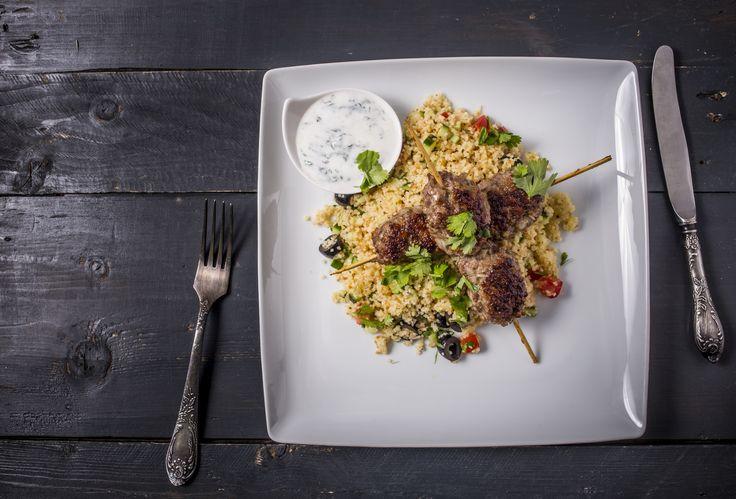 Fűszeres kebab - Kuszkusz salátával, mentás joghurttal | A kuszkusz hagyományosan Marokkó, Tunézia és Algéria nemzeti eledele. Alapja a búzadara, amit egészen kicsi gömbökké morzsolnak, majd több napig szárítanak. Az autentikus recept szerinti elkészítése nagyon érdekes és idő hatékony, hiszen amíg egy speciális, két részből álló gőzölő edény felső részében párolódik a kuszkusz, addig az alsó részében fő a leves, vagy puhul a bárány, csirke vagy éppen a zöldség. A kuszkusznak sós és édes…
