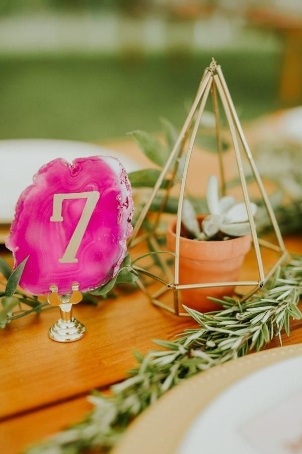 Gold pyramid plant holder + pink geode table number | Image by Jamie & Sarah Photography