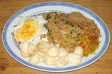 Nasi goreng geserveerd met een gebakken eitje, kroepoek, atjar, seroendeng en bawang goreng (gebakken uitjes). Een Indonesisch gerecht bereid door de Happy Chief Cook.