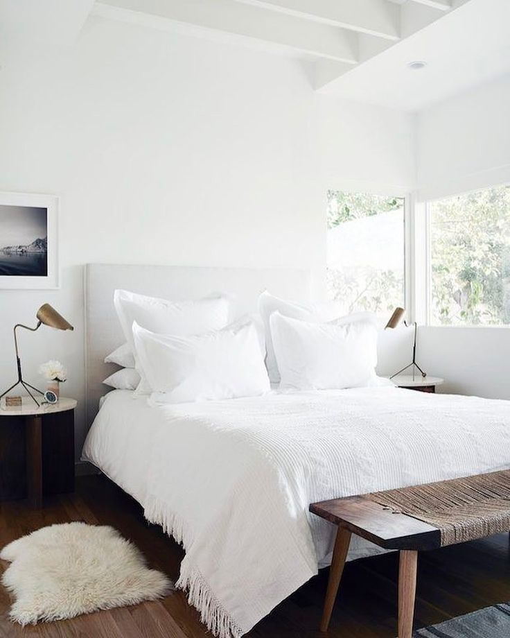 Minimal bedroom with white bed, bench, and faux fur rug