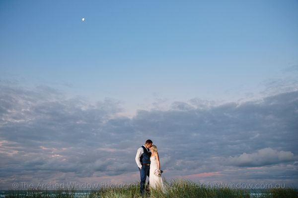wedding photos on the beach during sunset and a moonrise. Photography by The Arched Window.