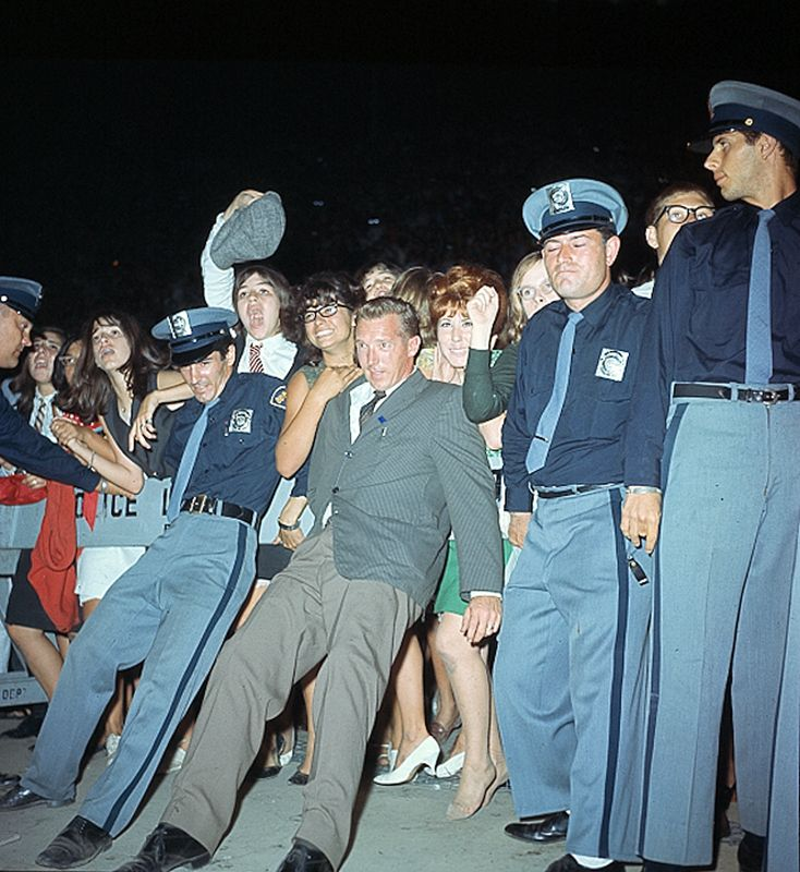 Police officers push back fans who stand behind police lines to see the Beatles in 1964.