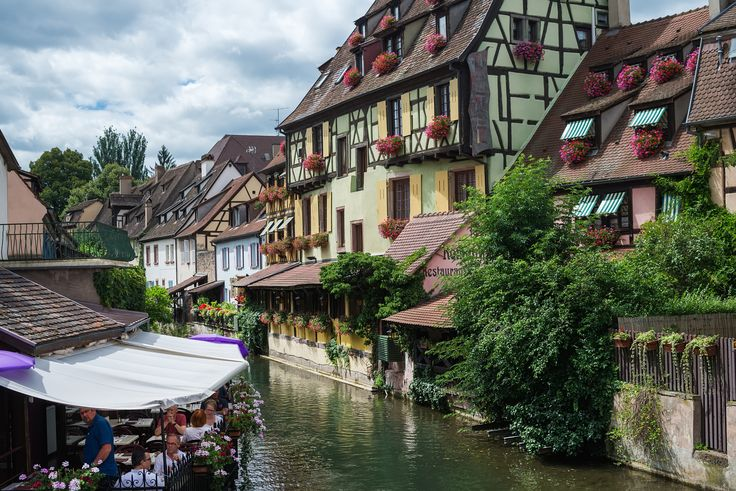 COLMAR, FRANCE - JUNE, 20: Colorful traditional french houses and a small restaurant terrace on the  - COLMAR, FRANCE - JUNE, 20: Colorful traditional french houses and a small restaurant terrace on the side of river Lauch in Petite Venise, Colmar, France