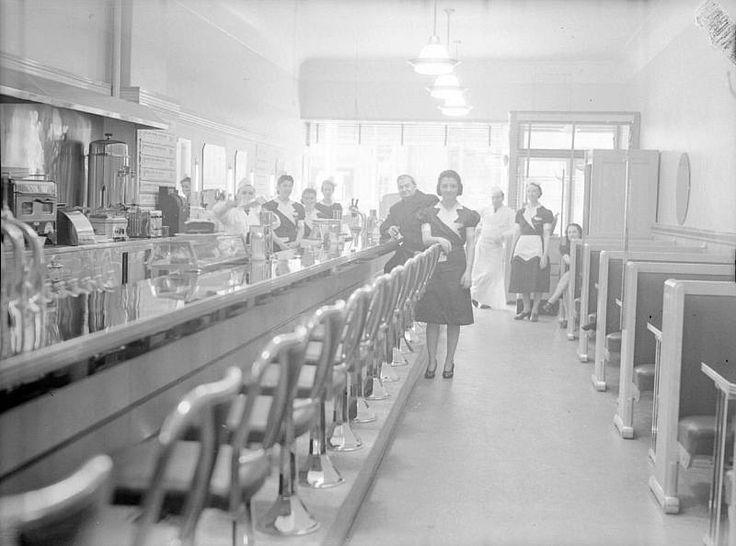 Le patron, les serveuses et les cuisiniers sont réunis restaurant Briton situé à l'intersection des rues Guy et Sainte-Catherine. Nous remarquons le comptoir, les tabourets, les fontaines de boissons gazeuses, la caisse enregistreuse et les banquettes. - 1942