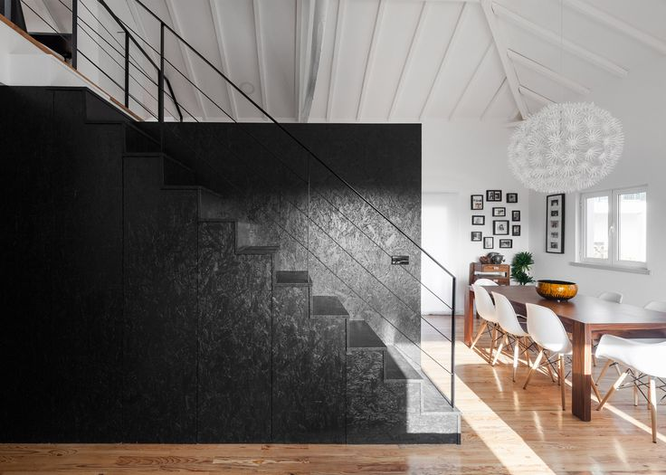 A black box built from oriented strand board houses the kitchen and bathrooms of this converted barn home in Portugal