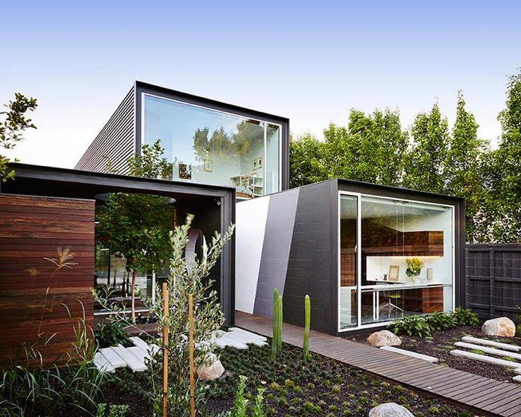 Maison conteneur de design moderne avec jardin de rocaille et allée en bois