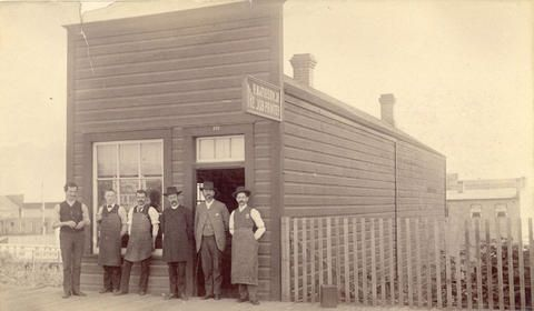 Exterior of the R. Mathison Job Printer building, 323 W. Hastings St.  Robert Mathison, Jr., is standing at the far right.  July 17, 1890.  Vancouver City Archives.