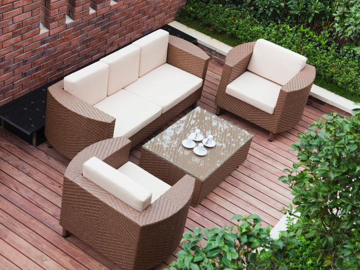 Sleek rattan chairs, sofa and coffee table make a sitting area on a deck. Shrubbery surrounds the deck, providing privscy.