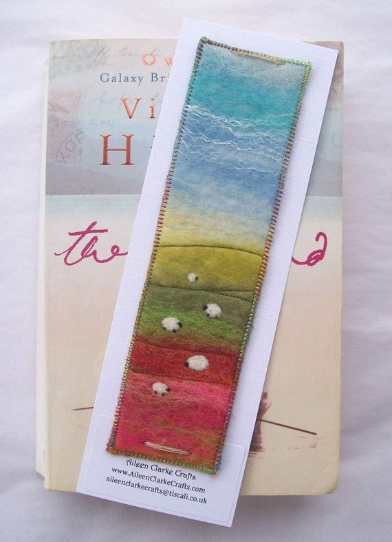 An original piece of Felt Art in the form of a bookmark. This little landscape features a wet felted background with needle felted sheep and a little bit of stitch here and there for added detail. The bookmark is backed with a lovely soft plaid effect flannelette and satin stitched round the edges to finish it off. Bookmark measures 4.5x18cm and comes tacked onto a white display card with an Aileen Clarke Crafts label. Handmade in Scotland