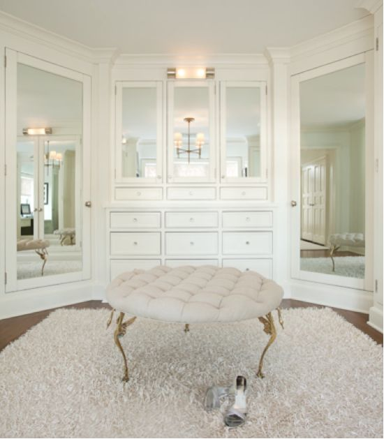 Ali Schwarz Design Group: Stunning Walk In Closet With Built In Cabinets,  Mirrored Doors And Tan Linen Round Tufted Ottoman With Brass Legs.