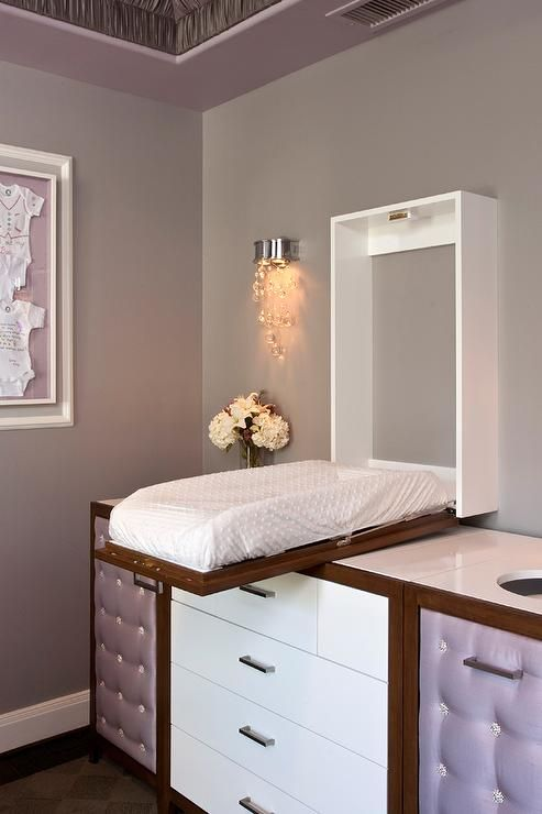 Glamorous gray and purple nursery features a concealed changing table that drops down over a dresser featuring white drawers accented with satin nickel pulls flanked by purple tufted upholstered cabinets located under diaper holes cut out from white countertops lit by a crystal beaded wall sconce mounted on gray walls.