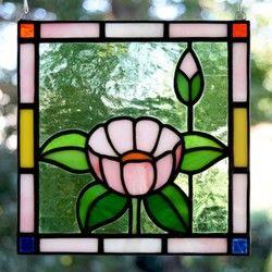 淡いピンクの花が愛らしいステンドグラス ミニパネルです。優しい印象で、クラシックな図案は、洋室はもちろん和の空間にも似合います。 パネル上部には吊り下げ用の金具が付いていますので、お手持ちのチェーンや紐で吊り下げて飾ることができます。陽のあたる窓際に吊り下げると、ガラスの色が鮮やかに(濃く)浮き上がり、とてもきれいです。お好みで飾る向きを変えていただけます。作品は自立しませんが、壁に立てかけたりお手持ちの皿立てに立てかけて飾ることも可能です。その場合は倒れて割れないよう布などを敷くことをお勧めします。 リビングボードの上や、飾り小窓、出窓などに飾っても素敵です。DIYが得意な方は、ドアや壁にはめこんたり額に入れて飾ってみてはいかがでしょうか。大きさ:たて約15cm×よこ約15cm×厚さ約3mm 重さ:約200g 素材:ガラス、鉛●ご購入の前に必ずご確認ください。作品はすべてハンドメイドの一点ものです。 ガラス作品のため、光のあたり具合によって色の見え方や透明感が違ってきます。…