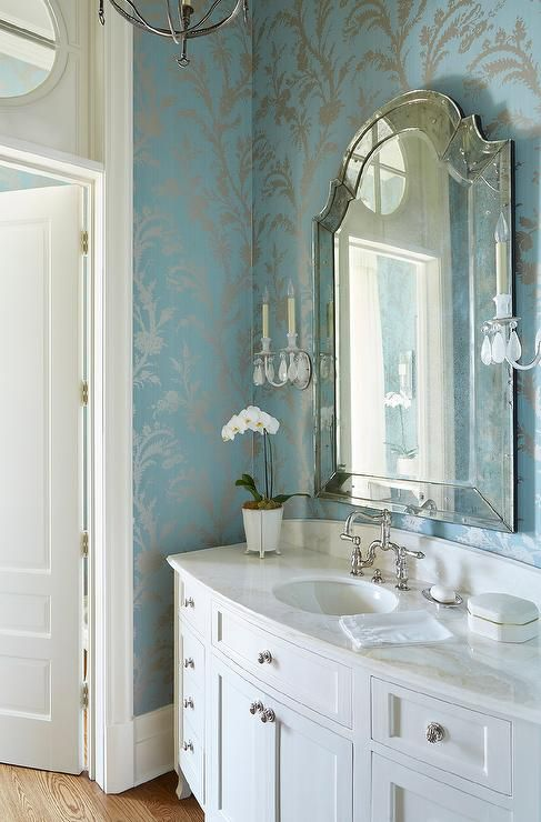 Silver and blue powder room features silver and blue metallic wallcovering lined with an arch venetian mirror lit by crystal droplets candle sconces placed over a white curved single washstand topped with white marble fitted with an oval sink and a polished nickel vintage faucet.