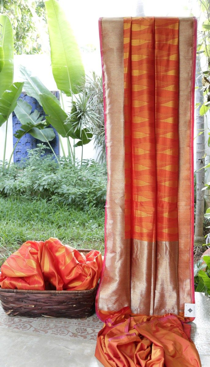 This Benares silk has spindle like pattern made with thread work placed close to each other in amber orange, orange and marigold orange. Both the pallu and border are simple in gold zari making it ...