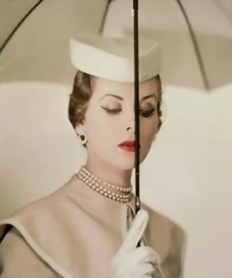 Let me count the ways...Cape coat, matching umbrella, a tidy hat, kid gloves, red lipstick, triple-strand pearl choker, seed pearl earrings (no diamonds before six) and grooming.  Photo by Erwin Blumfeld