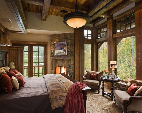 Timber house bedroom in mountain country with rustic fireplace and plenty of glass to take in the views - note the flatscreen above the fireplace