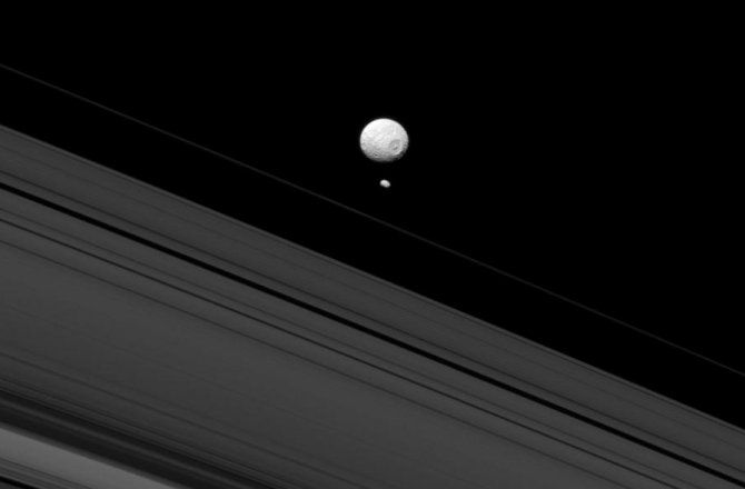"""Saturn's moon Pandora looms behind Mimas, the """"Death Star moon,"""" in this photo from NASA's Cassini mission that highlights Mimas' huge 86 mile (139 kilometer) wide circular Herschel Crater --the scar of a violent, giant impact from the past."""