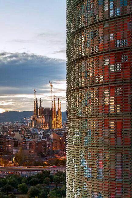 New vs Classic Architecture. Modern building -Torre Agbar- in Las Glorias upfront vs La Sagrada Familia at the bottom of the image. Barcelona. Catalonia.