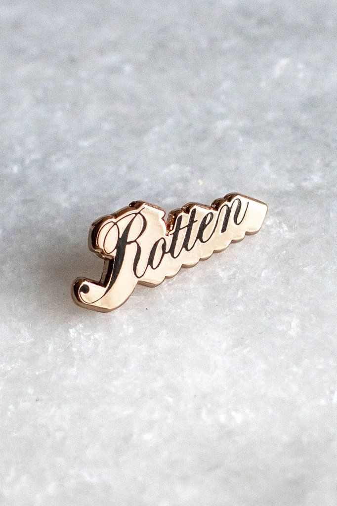 """Beautiful and rotten. 1"""" wide lapel pin in rose gold metal with hard enamel text. Designed in house for Stay Home Club by Olivia Mew."""