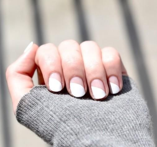 If you've outworn your standard white mani, try painting just half of each nail white. These white diagonal nails are chic and easy. For a sharp line, use tape to mask off the bottom of each nail. And in no time, you'll have a modern nail look that pairs well with any style.