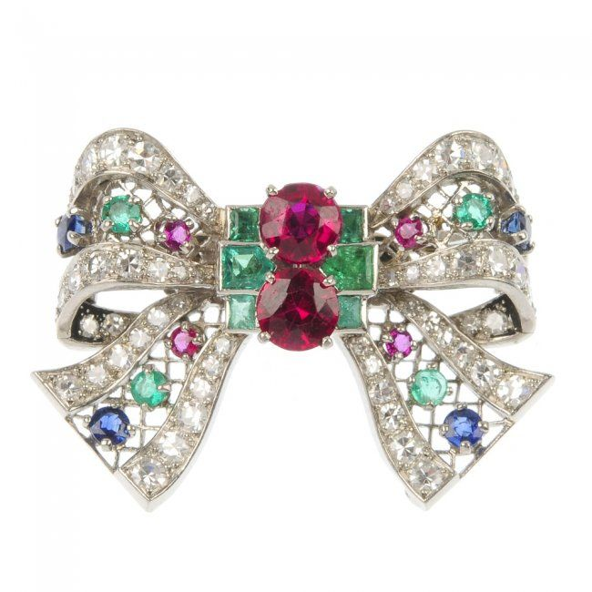 MOUNTED BY BOUCHERON - a mid 20th century multi-gem bow brooch. The circular-shape synthetic ruby and graduated square-shape emerald central cluster, to the lattice bow with single-cut diamond sides and circular-shape ruby, emerald and sapphire accents. Signed Monture Boucheron. French assay marks