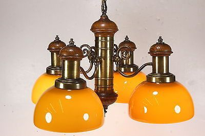 This is a vintage 4-light ceiling fixture made by Thomas Industries It has a bit of a nautical feel. It is composed of oak wood with brushed-brass looking metal decorative elements. The fixture featur