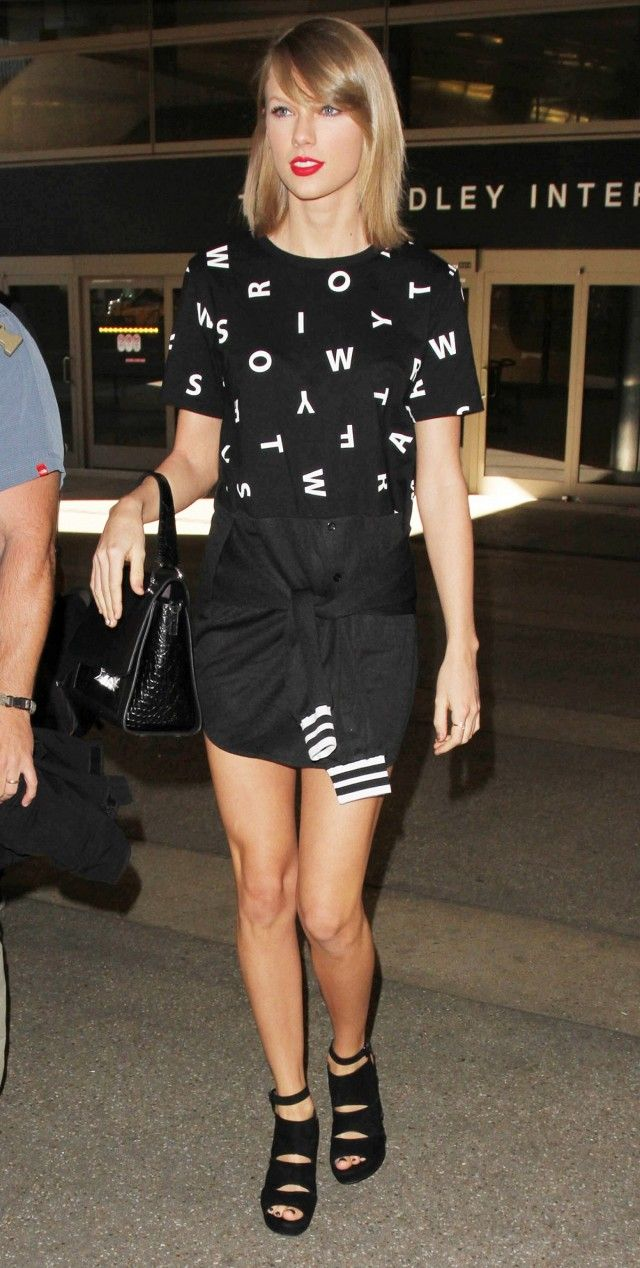 Taylor Swift wears a printed top, miniskirt, top-handle bag, and platform sandals