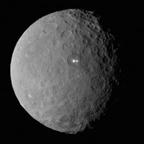 Cérès vue par Dawn le 19 février 2015, montrant des taches claires de nature inconnue, au fond d'un cratère. Ceres est la plus petite planète naine reconnue du Système solaire ainsi que le plus gros astéroïde de la ceinture principale ; c'est d'ailleurs la seule planète naine située dans la ceinture d'astéroïdes. Elle fut découverte le 1er janvier 1801 par Giuseppe Piazzi et porte le nom de la déesse romaine Cérès.