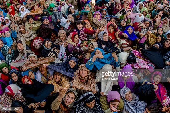 Kashmiri Muslim devotees look towards a cleric displaying the holy relic believed to be the whisker from the beard of the Prophet Mohammed, at Hazratbal shrine on the Friday following, Eid-e-Milad ,...