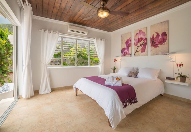 Master bed room: new door onto patio (replacing a window), ceiling, tiles, bedding, ceiling fan, lights, artwork, and fresh coat of paint!  #saba #visitsaba #julianashotel #remodel #renovation #makeover #orchid #orchidcottage