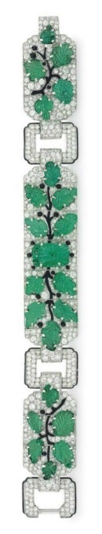 CARTIER - AN ART DECO DIAMOND, EMERALD, ENAMEL AND ONYX BRACELET, CIRCA 1925. The three single and old-cut diamond panels, with carved emerald leaves, black enamel and onyx branch detail, joined by single and old-cut diamond open links with black enamel borders, mounted in platinum. Signed Cartier and numbered. #Cartier #ArtDeco #bracelet