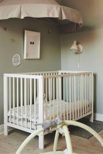 Crie uma área para o bebé com um berço que se converte numa cama, sob um acolhedor dossel cinzento, decorado com estrelas douradas.