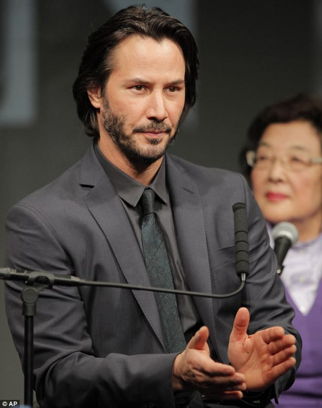 Well-groomed: Keanu Reeves is smart with slicked back hair and a grey suit at a press conference in Tokyo