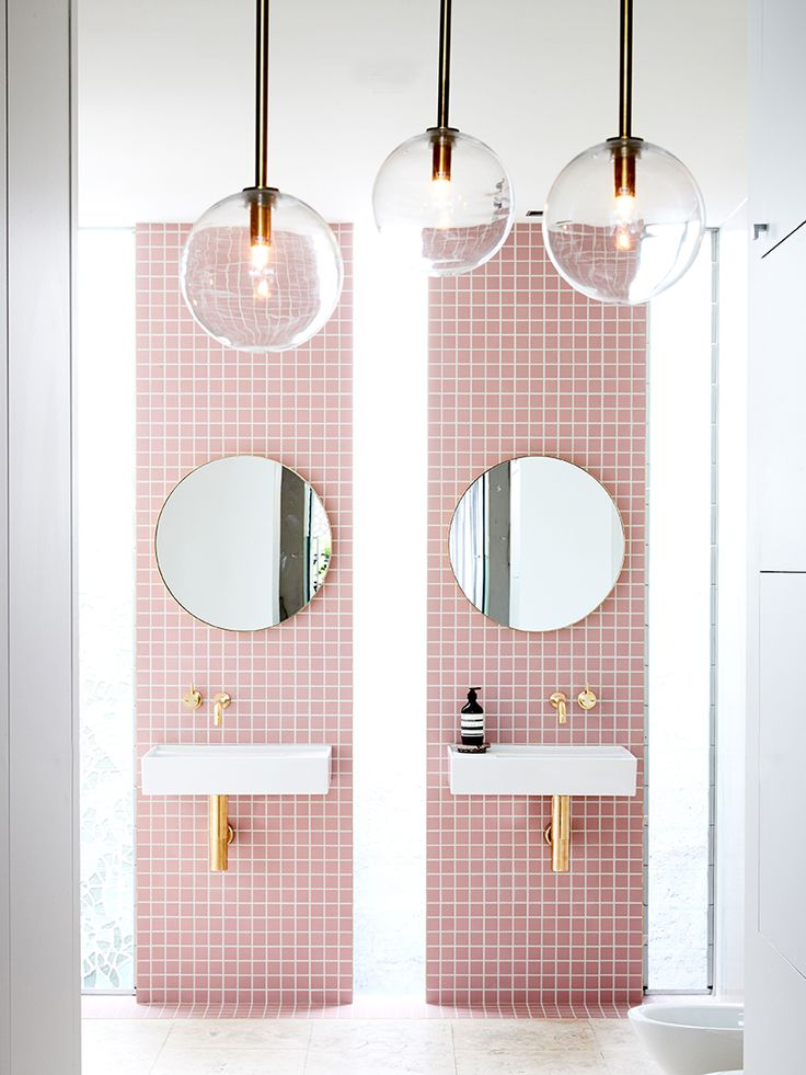 My dream bathroom came to life in Rebecca Judd's home. The square pink tiles selectively line the bathroom creating two stripes for each vanity. The shiny gold hardware beautifully reflect the lighting in the room. Three glass pendant lights hang from the ceiling as does a gold shower head. There's also a gorgeous marble wall to the right of the …
