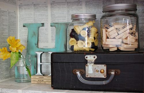 Bookshelf decor.  Love the dominoes and chess jar.  Love the book page covered bookshelf.