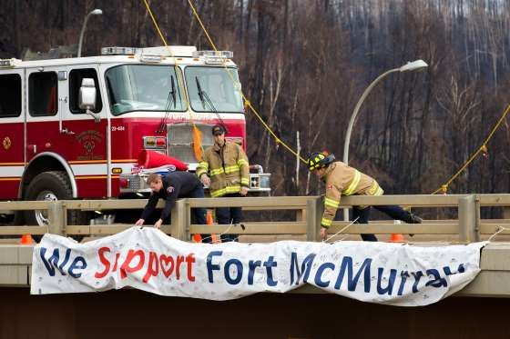 "Wednesday, June 1, 2016 | Fort McMurray firefighters fix a sign that reads ""We Support Fort McMurray"" on an overpass above Memorial Drive in Fort McMurray 