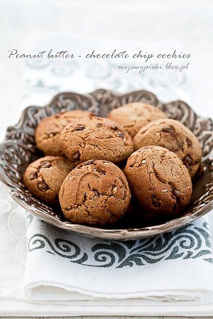 Ciastka z masła orzechowego z czekoladowymi drobinkami Składniki na około 30 ciastek (2 blaszki):      1,5 szklanki mąki pszennej     1 łyżeczka sody oczyszczonej     1 szklanka masła orzechowego (około 300 g)     60 g masła, w temperaturze pokojowej     1 szklanka miałkiego brązowego cukru     2 duże jajka     1 łyżeczka ekstraktu z wanilii     240 g czekoladowych drobinek (chocolate chips) lub drobno pokrojonej czekolady gorzkiej lub mlecznej