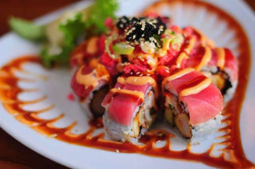 Sushi: the roll has shrimp tempura inside with sweet eel, cream cheese, tempura flakes, avocado, masago, scallions, and topped with red tuna