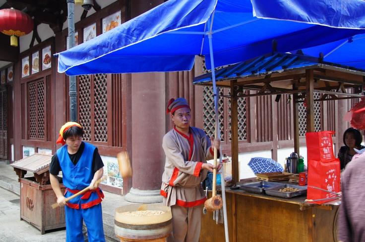 Een stel maakt een soort platte snoep op de markt voor de Yungang grotten . Datong, China