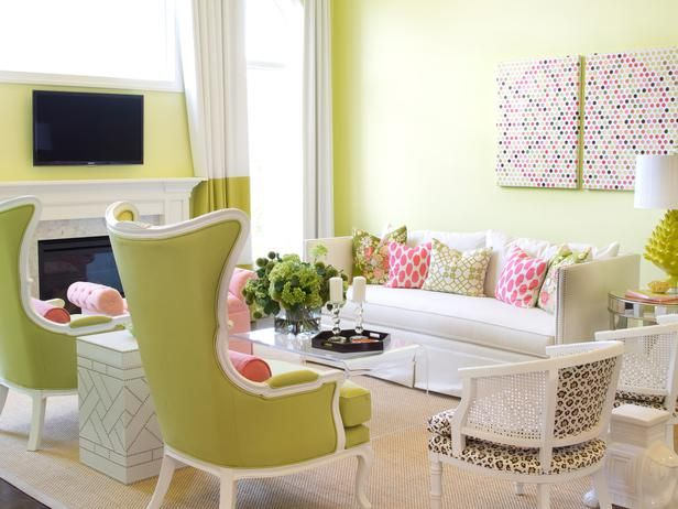 Designer Alisha Gwen pops for pure color in this cheery living room. Oversized lime green wingback chairs set a whimsical tone while punches of pink throughout give the room a romantic feel. White lacquered frames, rather than traditional stained wood, give the chairs a contemporary look.