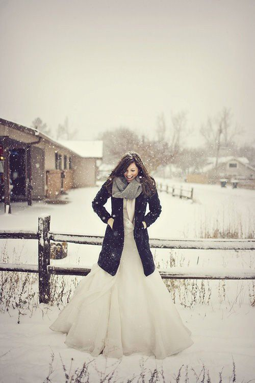 A beautiful bride enjoying the snow - wear the groom's coat outside to get a fun look #winter #wonderland #wedding
