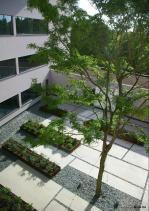 bioversneller van Sumprojects - centrum voor biotechnologie met een halfondergrondse open parking waarboven twee gebouwvleugels met onderzoekslaboratoria en kantoren zweven rondom een groen atrium