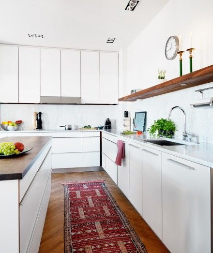ok, all-white cabinets, even with white counters, still look pretty great, especially when warmed up with a persian rug and some wood accents.  Oh, and wood floors, which we do not have in our kitchen
