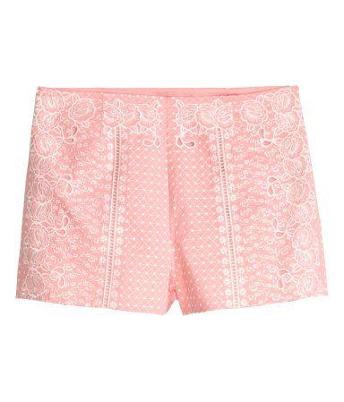 Rosa. En kort shorts i vevd bomullskvalitet med brodert mønster. Shortsen har høy midje og korte ben. Skjult glidelås i siden. Fôret.