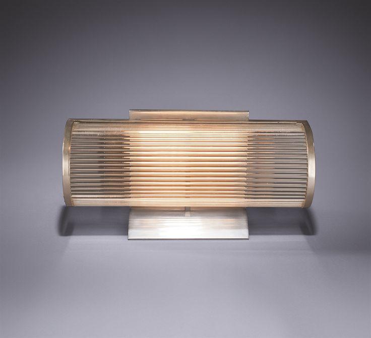 Louis Sognot (1892-1969) et Charlotte Alix (1897-1987) Lampe de table, vers 1930 Le cache-ampoule semi cylindrique en laiton nickelé, enserrant une série de baguettes tubulaires en verre incolore, monté par devant un pied en aluminium plié en V, incurvé à la base Hauteur : 21 cm. (8¼ in.) ; Longueur : 40,2 cm. (15 7/8 in.) ; Profondeur : 18 cm. (7 in.)
