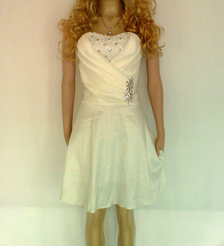 Vestido corto blanco, falda rotonda y detalle de pedrería plateada.