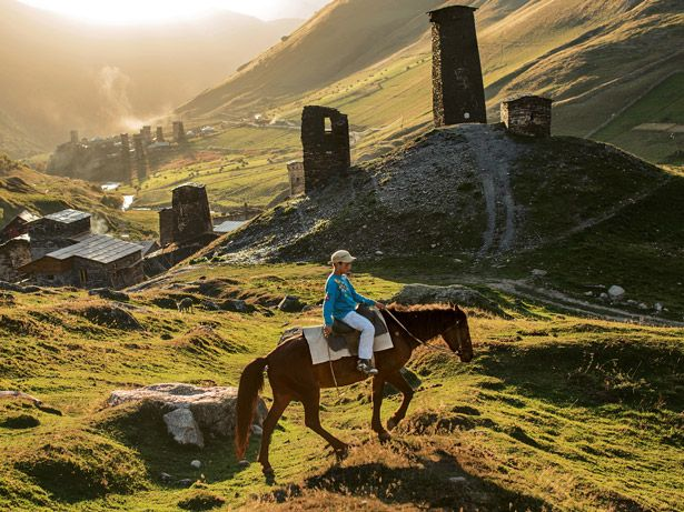 This Photo shows a contrast between old and new. A child on traditional animal power but in modern clothing, surrounded by towers and ruins built many generations before their own