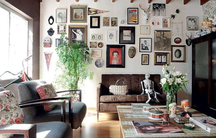Para não gastar com pintura ou papel de parede, cubra as paredes com tudo o que tiver, como quadros, fotografias, louças e cabeças de bicho. Assim você esconde imperfeições na pintura e tem um visual incrível. Ideia da estilista Patricia Grejanin