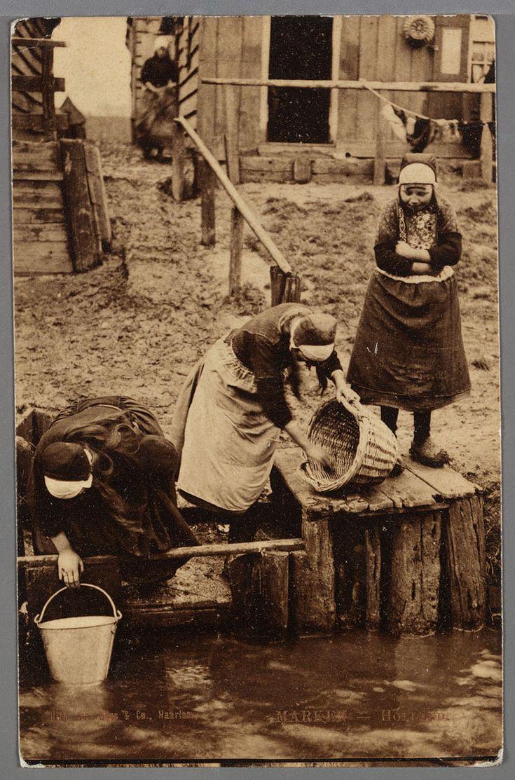 Drie vrouwen in werkdracht bij de boenstoep, ca. 1910. Rechts haalt een vrouw een emmer water uit de sloot. Het meisje rechts is Niesie Schouten. Op de achtergrond wasgoed en huisjes. 1905-1915