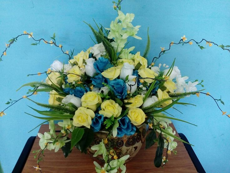 Blue, yellow and white arrangement with touches of green in a Chinese vase